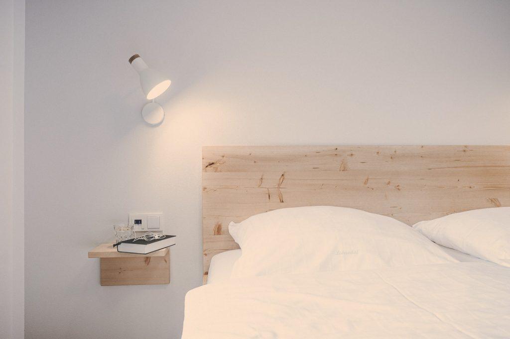 Der Lederer Hof Tegernsee - Bett Detail Holz und Weiß