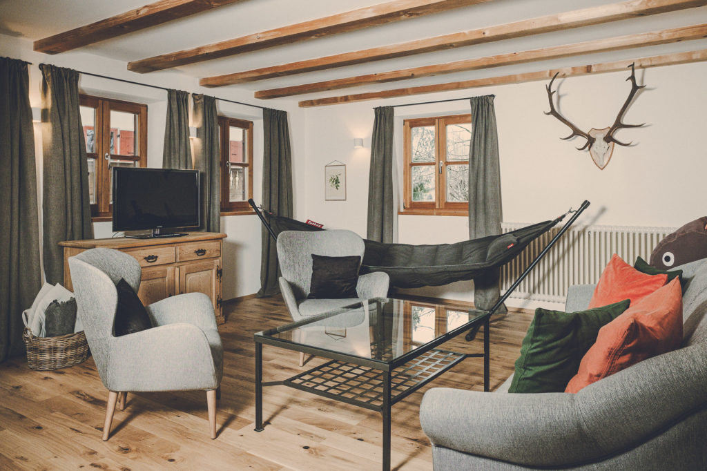Der Lederer Hof Tegernsee - Das Platzhirsch Apartment Wohnzimmer mit Fatboy Hängematte
